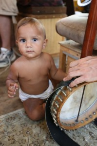 Baby and banjo on board at Camp Woolman.