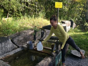 Ally collects water from a spring in Dixmont, ME.