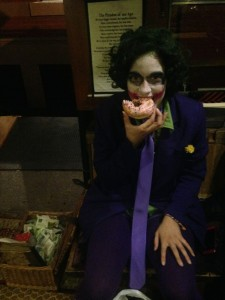 The Joker eats a donut on Halloween in SoHo.
