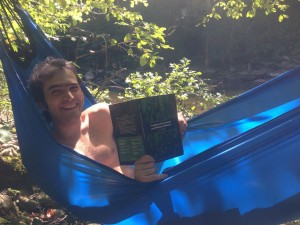 Reading about Traditional Huamn Economy in a hammock donated to the tea bus by Behold Bungee Hammocks.